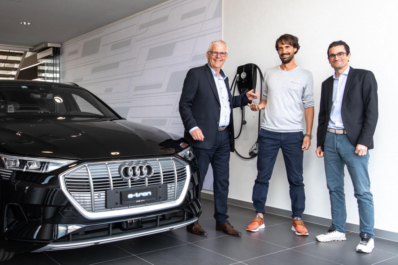 Caspar Coppetti (au centre) se voit remettre sa nouvelle Audi e-tron de de Thomas Huser (à gauche), directeur du site AMAG Baden, et de Livio Piatti (à droite), directeur marketing d'Audi Suisse.